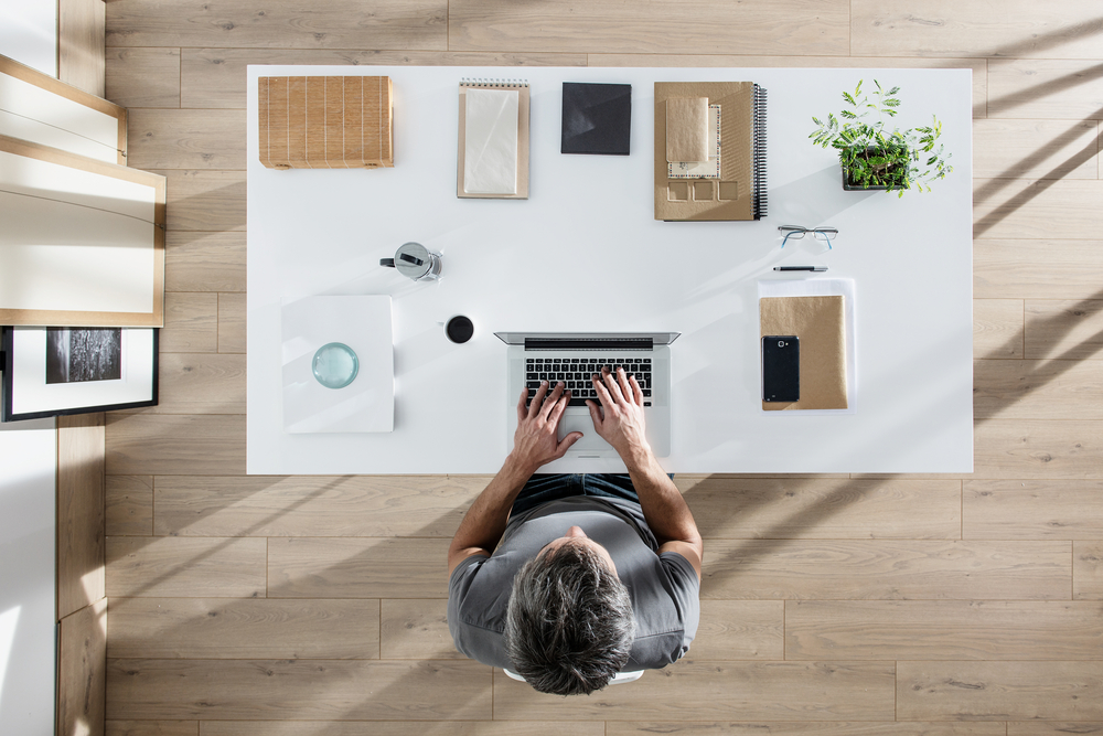 man-sitting-at-organized-desk-in-home-office