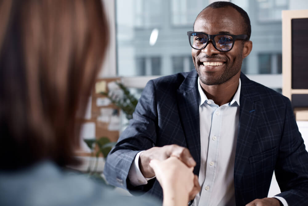 Young job candidate shaking hands with interviewer
